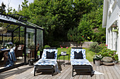 Two loungers on sunny wooden deck between conservatory and house