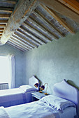 Twin beds with lilac headboards below wood-beamed ceiling