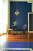 Round table and various chairs in front of dark blue wall