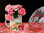 Rosafarbene Rosen in einer Tasse mit Rosenmotiv vor schwarzem Grund