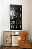 Wooden chair, pictures leaning against wall and electrical switchboard on wall