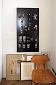 Holzstuhl, angelehnte Bilder auf dem Boden und Strompanel an der Wand
