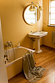 Bathtub and pedestal sink below round mirror in retro bathroom with painted walls