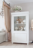 Old pictures and soup tureens in white cabinet with glass door