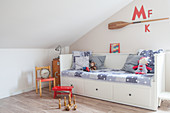 Bed with drawers below under sloping ceiling in child's bedroom