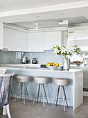 Barstools at island counter with glossy white cabinets