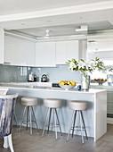 Barhocker an der Kücheninsel mit weißen Hochglanzfronten