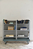 Books on simple metal shelves on castors against white wall