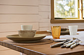 Crockery, cutlery and glasses in soft natural shades on table