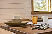 Geschirr, Besteck und Gläser in soften Naturtönen auf dem Tisch