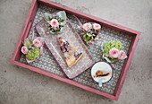 Kleine Blumensträußchen und Kuchen auf einem Tablett