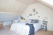 Simple attic bedroom with wood-clad walls