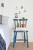 Stacked magazines on old blue chair used as bedside table