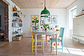 Colourful chairs around old dining table in dining room