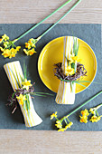 Easter place setting: yellow plate and yellow and white striped napkin with Easter wreath