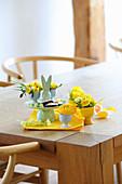 Hasen-Etagere und Eierbercher mit Frühlingsblumen auf Tisch