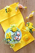 Hasen-Etagere mit Eier-Konfekt und Eierbecher mit Frühlingsblumen auf gelbem Tuch