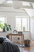 Small workspace below window in white bedroom
