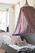 Cosy wooden bed with dusky pink canopy in child's bedroom