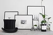 Grünpflanze, Eiffelturm-Miniature, eingerahmte schwarz-weiße Fotos und Zylinder auf Ablage