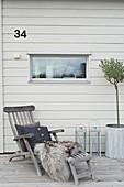 Liegestuhl mit Kissen und Fell vor der Hauswand mit Hausnummer