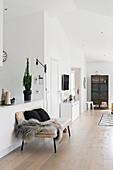 Bank mit Fell und Kissen vor der offenen Küche im Wohnraum