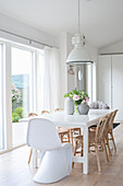 Designer chair and rattan chairs around table in white dining room