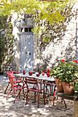 Tisch mit Vintage Stühlen auf Terrassenplatz vor provenzalischem Haus