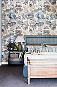 Double bed with bed headboard and bedside table in front of silver-gray wallpaper
