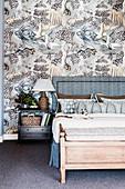 Doppelbett mit Bettkopfteil und Nachttisch vor silber-grau tapezierter Wand