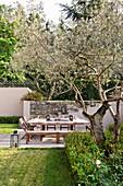 Gedeckter Tisch mit Stühlen und Bänken im mediterranen Garten