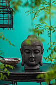 Head of Buddha on black table and leafy tendrils against turquoise wall