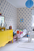 Yellow sideboard and metal bed in child's bedroom with blue and white wallpaper
