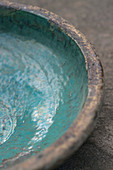 Close-up of rustic stoneware dish with turquoise glaze