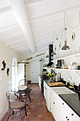 Seating area in narrow country-house kitchen with sloping wood-beamed ceiling