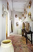 Collection of sunburst mirrors in hallway with honeycomb floor tiles