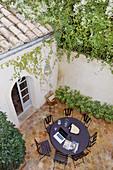 View down onto round garden table in Mediterranean courtyard