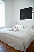 Dog on double bed with white bedspread below black painting in bedroom with wooden floor