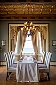Precisely positioned upholstered chairs around long dining table in classic dining room