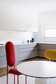 Round table and designer chairs in white fitted kitchen