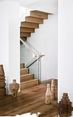 Elegant staircase with wooden staircase and glass balustrade, wooden sculptures on the floor