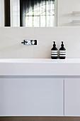 White vanity and black soap dispenser in the bathroom