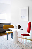 Round table and designer chairs against white wall