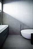 Designer bathroom with bathtub and gray tiles