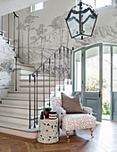 Elegant grey-and-white foyer with landscape painted along staircase