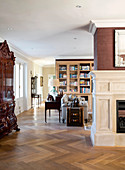 View past fireplace and antique cabinet into open-plan interior with bookcases