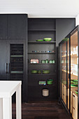 Black fitted kitchen up to the ceiling and showcase with green dishes
