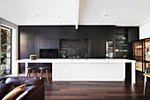 Long white kitchen island in front of an open kitchen with black fronts