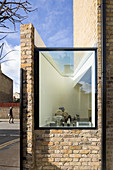 Kitchen window of modernised brick house below blue sky