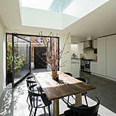 Dining table below skylight and open swivel door leading to courtyard